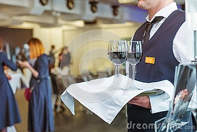 Professional waiter in uniform holding a tray with glasses of vine at business event. Catering or celebration concept. Service at