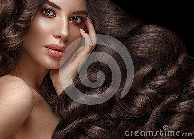 Beautiful brunette model: curls, classic makeup and full lips. The beauty face.