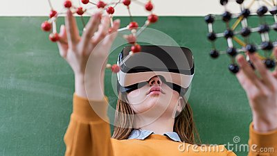 stock image of female student wearing virtual reality glasses, holding molecular structure model. science class, education, vr, new technologies.