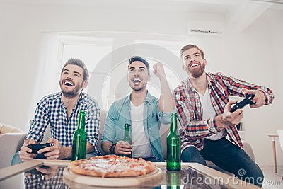 Yes! Team of winners! Bachelor men`s life. Low angle of three happy joyful men, sitting on sofa and playing video games with beer