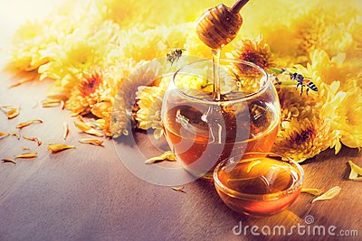 Honey in glass jar with bee flying and flowers on a wooden floor