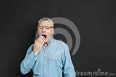 Horizontal photo of mature unshaved man 60s with grey hair weari