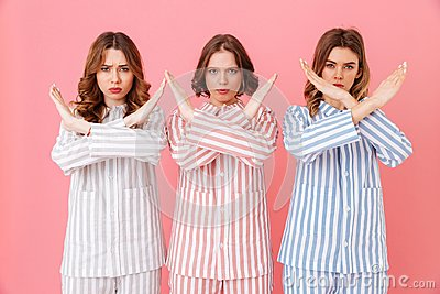 Portrait of three beautiful young girls 20s wearing colorful striped pyjamas showing crossed hands no gesture meaning deny
