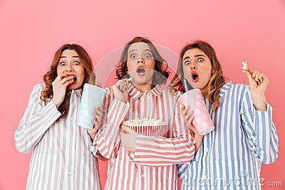 Three young girls 20s wearing colorful striped pyjamas expressing excitement or thrill while watching movie at slumber party and