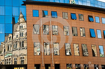 Reflection of an old building in new glass building. Old architecture versus modern reflected in glass. City of Liberec