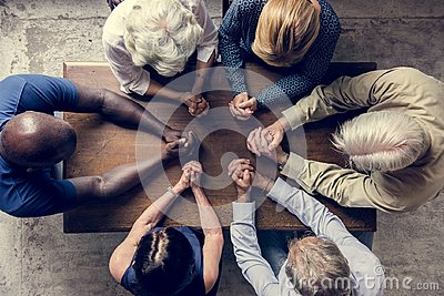 Diverse religious people praying together