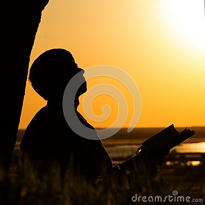 Silhouette of a man reading the Bible in the field, male praying to God in nature, the concept of religion and spirituality