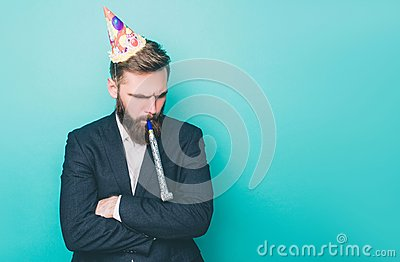 Sad guy is standing and looking down. He is upset. Man is holding a wistle in his mouth and has a birthday hat on the
