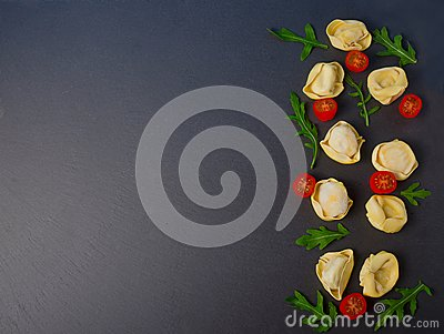 Frozen tortellini on the black background. Italian tortellini with fresh ricotta leaves and tomatoes on a black stone board.