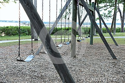 Empty abandoned swings in a local park reflect our forgotten childhood