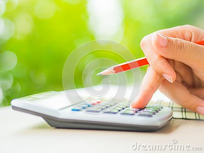 Woman hand working with calculator and holding red pencil