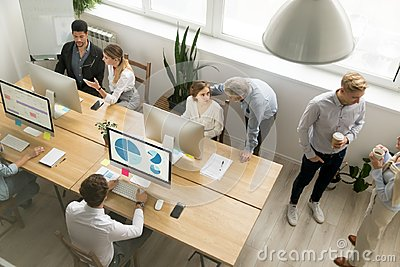 Office employees working together sharing desk using computers i