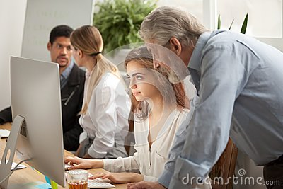 Aged executive manager supervising computer work of intern in of