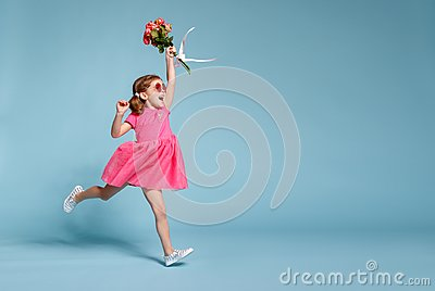 Funny child girl runs and jumps with bouquet of flowers on color