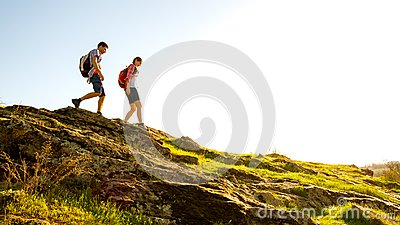 stock image of young happy couple hiking with backpacks on the beautiful rocky trail at sunny evening. family travel and adventure.