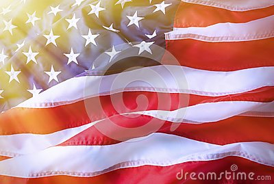 American flag background. Brightly lit American flag. Sunlight, sunflare on the right side.