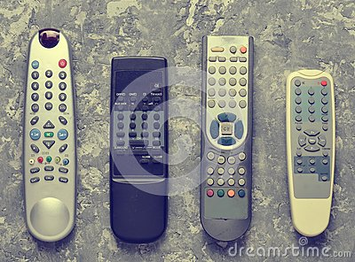 Many TV remotes on a gray concrete table. Top view.