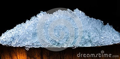 Pile of crushed ice cubes in wood bucket on dark background with copy space. Crushed ice cubes foreground for beverages, beer