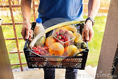 Online grocery shopping service concept - delivery man with food