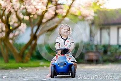 Cute little baby girl playing with blue small toy car in garden of home or nursery. Adorable beautiful toddler child
