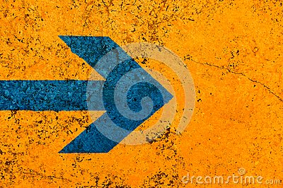 Blue arrow direction sign over vivid bright orange color stone wall with imperfections and cracks