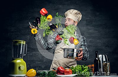 Man cook holds a pan with vegetables flying in the  air.