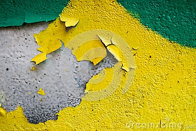 Texture of a two-color yellow and green old shabby concrete wall with bulbous peeling varicoloured paint, pits and patterns