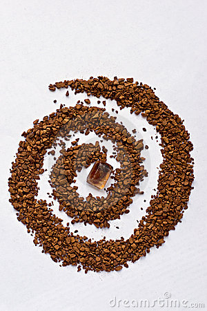Spiral of coffee with a cane sugar cube on white