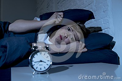 Young beautiful woman lying in bed late at night suffering from insomnia trying to sleep