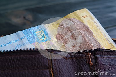 Old shabby leather wallet with Ukrainian hrivna bill on wooden t