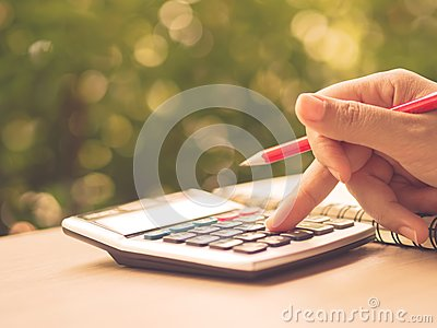Soft focus retro woman hand working with calculator and holding red pencil