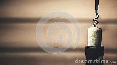 Corkscrew and bottle of wine on wood background.