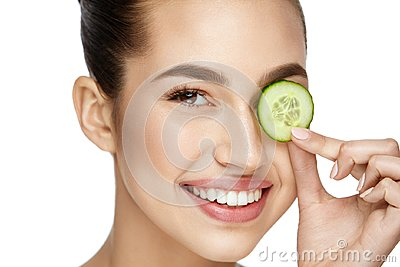 Eye Skin Care. Woman With Natural Makeup Using Cucumber