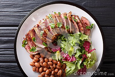 Grilled Carne Asada steak with salad and beans close-up. horizon
