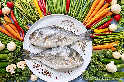 Dorada fish on white dish with colorful vegetables around. Dorad