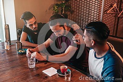 Supportive young men encourage their brokenhearted friend. Arabian guys cheer him up in restaurant. Friendship concept.