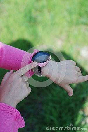Pink Smartwatch Phone o nLittle girl& x27;s Hand. Kid Using pink Intelligent Phone. Summer time Otside.