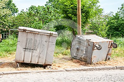 Two big old metal dumpster garbage cans on the street damaged by vandals