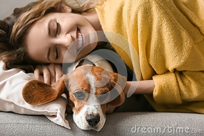 Young woman with her dog resting on sofa