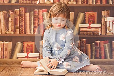 Adorable little bookworm girl reading books.