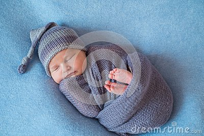 Tiny Sleeping Newborn Baby covered with rich purple coloured wrap