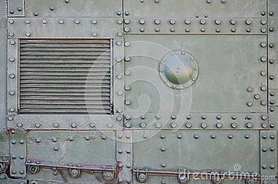 The texture of the wall of the tank, made of metal and reinforced with a multitude of bolts and rivets. Images of the covering of