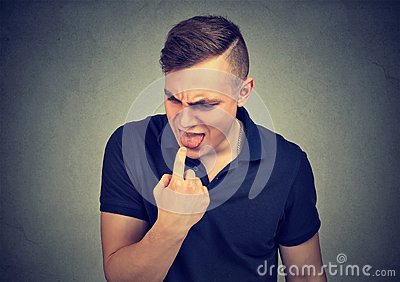 Disgusted man with finger in mouth ready to throw up