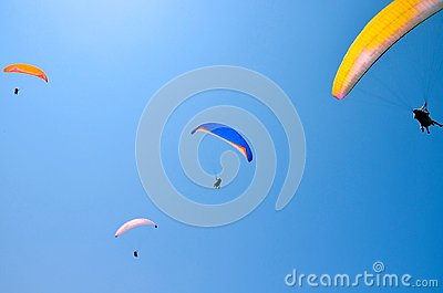 Paroplane group flying against the blue sky.Extreme sports, enjoy life, appreciate the time, tandem paragliding, controlled pilot