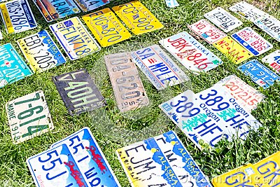 Different USA car retro license plates at flea market. Vintage vehicles registration numbers lay on grass at swap meet