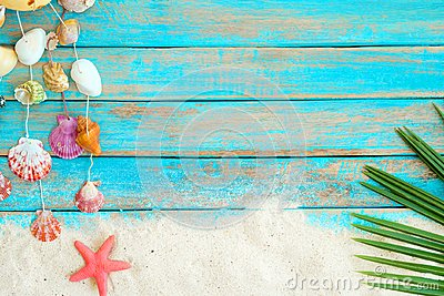 Summer background with beach sand, starfishs coconut leaves and shells decoration hanging on blue wooden background.