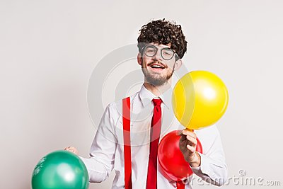 Portrait of a young man with balloons in a studio.