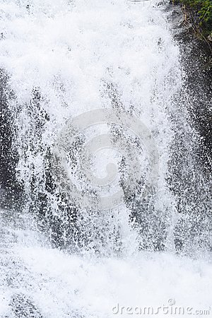 Close up of Forceful Flow of Water with Sprinkling of White Drops