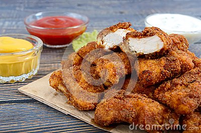 Chicken nuggets. Pieces of deep-fried crispy meat, on paper with different sauces on a wooden table.