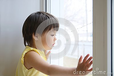 Little girl looking out the window longing for some sunshine. child sitting home at rainy day